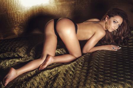 desnudo artistico: Sexy mujer morena con un cuerpo perfecto posando en la cama, mirando a la cámara