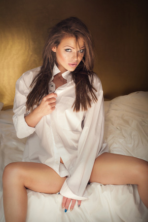 Elegant beautiful woman wearing white shirt posing in bedroom, looking at camera