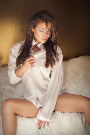 Elegant beautiful woman wearing white shirt posing in bedroom, looking at camera