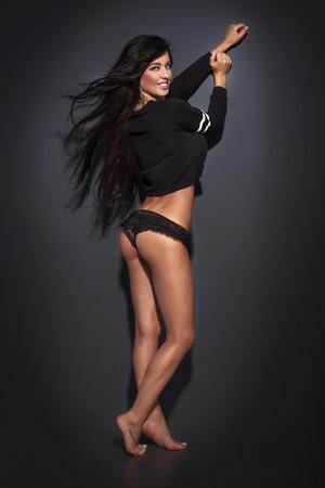 Slim beautiful brunette woman posing in lingerie, smiling, looking at camera Stock Photo