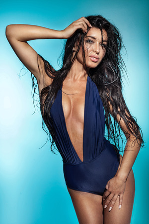 Sexy beautiful brunette woman posing in fashionable swimwear with wet hair, looking at camera.