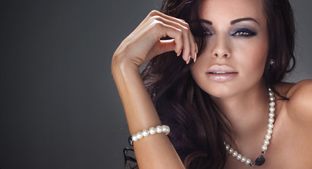 Beauty portrait of attractive brunette woman with elegant makeup, wearing perals jewelry. Girl looking at camera.