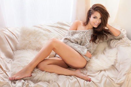 Beautiful smiling brunette woman with long slim legs posing in bedroom, relaxing Stock Photo