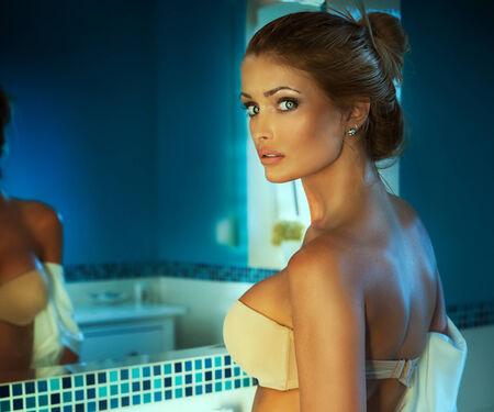 beauty breast: Portrait of sensual woman in bathroom. Girl looking at camera.