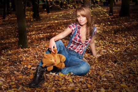 Fashionable blonde beautiful woman posing in autumn scenery, holding teddy bear photo