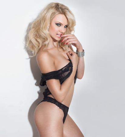 mujer rubia desnuda: Mujer sexy rubia posando sobre fondo blanco en ropa interior negro, mirando a la c�mara. Foto de archivo