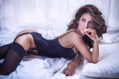 Sinnliche schöne Frau mit perfekten schlanken Körper posiert im Schlafzimmer mit schwarzen sexy Dessous. Standard-Bild - 34889299