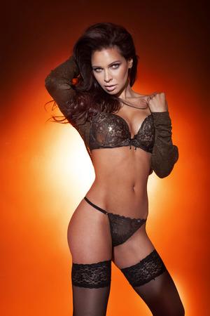 erotico: Sensuale bella donna bruna posa in lingerie sexy, guardando a porte chiuse.