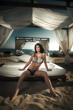 Beautiful brunette woman posing on the beach at sunny day, wearing fashionable swimwear photo
