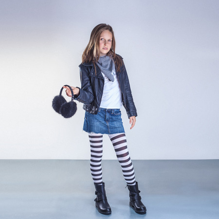 Fashionable young teenager girl posing in studio, looking at camera.
