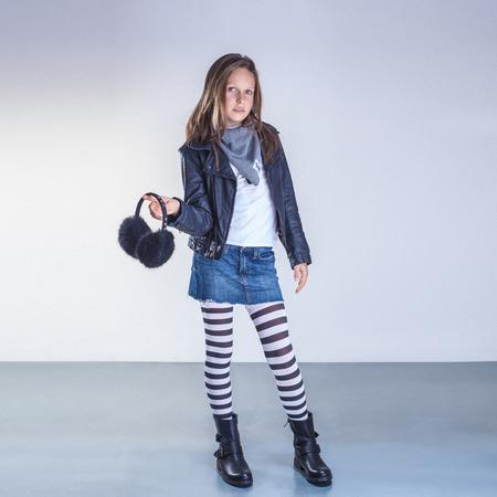 La mode jeune adolescent fille posant en studio, regarde la caméra.