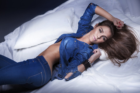 Sensual young woman posing in jeans clothes, lying in bed. Girl looking at camera.