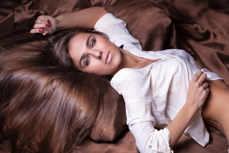 mujeres jovenes desnudas: Delicado joven y bella mujer morena en la cama, mirando a la cámara. Chica con el pelo largo sano.