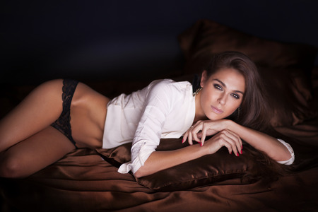 young girl nude: Romantic brunette attractive woman lying, sensual scene. Stock Photo