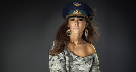 Conceptual portrait of beautiful sexy brunette woman in cap. photo