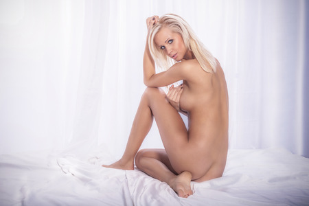 nude girl sitting: Sexy blonde woman in bed, looking at camera. Perfect body.
