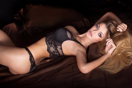 Sensual blonde woman posing in fashionable lingerie. Girl looking at camera. Studio shot. Stock Photo