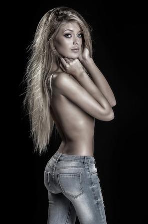 mujer desnuda: Mujer rubia joven hermosa que presenta en pantalones vaqueros. Chica con el pelo largo sano.