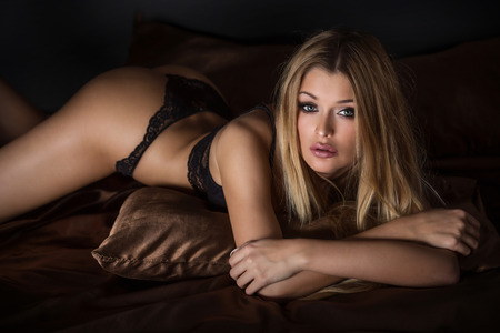 nude female figure: Sensual blonde woman lying in bed, wearing sexy lingerie. Girl looking at camera. Stock Photo