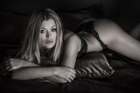Sinnliche blonde Frau im Bett liegend, mit sexy Dessous. Mädchen Blick in die Kamera. Standard-Bild - 34415755