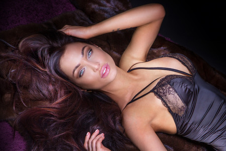 pretty woman face: Delicate sexy brunette woman lying in lingerie, relaxing.