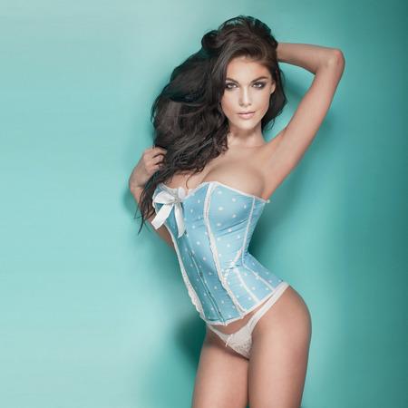 belle brune: Sensuelle femme brune avec un corps parfait posant en studio, regardant la caméra, Fille en lingerie.