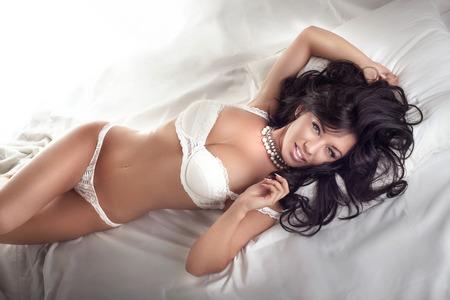 Sexy Brünette Frau mit perfekten Körper posiert in Dessous im Bett liegen. Standard-Bild - 36302761