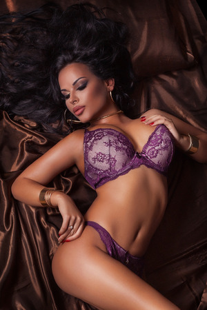 Sexy brunette woman with perfect body posing in lingerie lying in bed.