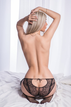 naked girl black hair: Beautiful blonde woman with perfect body posing in sexy lingerie, showing naked back.