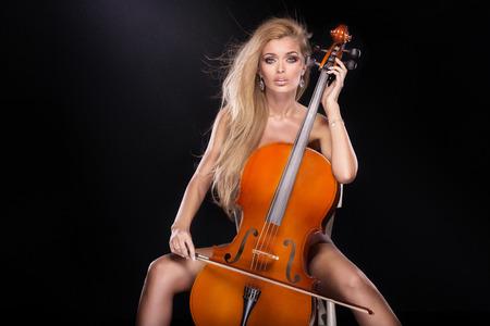 desnudo artistico: Atractivo sexy músico que toca el violoncelo. Mujer desnuda con el pelo largo mirando a la cámara. Foto de archivo