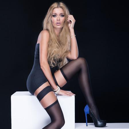 long shot: Sexy woman with long slim legs wearing stockings, looking at camera. Studio shot.