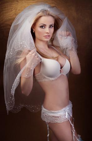 Beautiful sexy blonde bride posing, looking at camera. Stock Photo