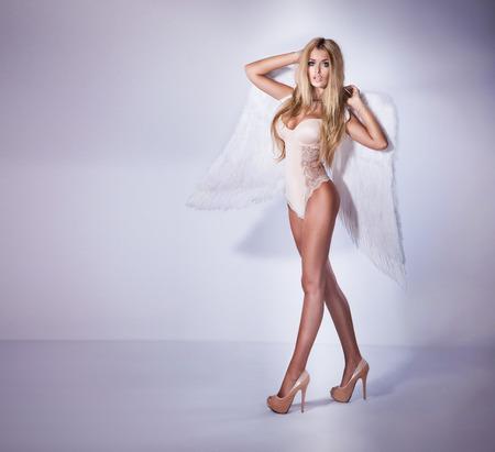 voluptuosa: Hermosa mujer rubia sexy posando con alas de ángel.