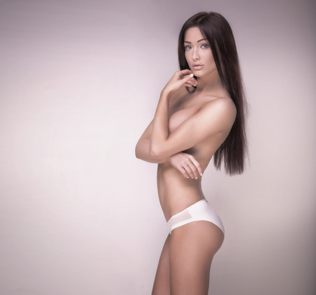topless brunette: Delicate perfect brunette woman posing naked in studio. Girl with long healthy hair looking at camera.