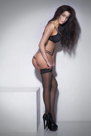 cuerpo femenino perfecto: Sexy hermosa mujer morena en ropa interior posando. Chica con el pelo largo y rizado. Estudio de disparo.