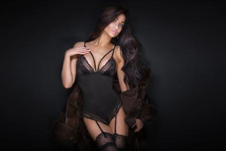 Sexy beautiful brunette woman in lingerie posing. Girl with long curly hair. Studio shot. Black background. Foto de archivo
