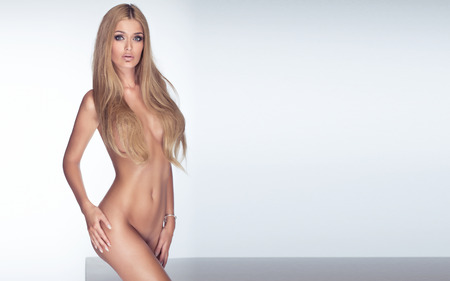 naked young girl: Sensual beautiful woman with perfect slim body posing naked, looking at camera. Studio shot. Stock Photo