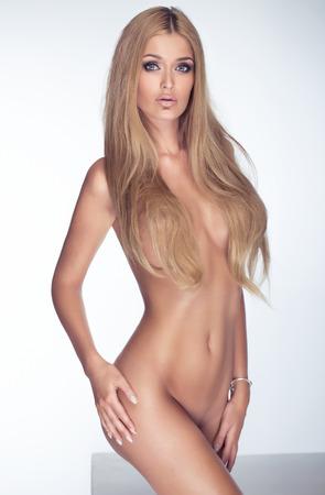 Sensual beautiful woman with perfect slim body posing naked, looking at camera. Studio shot. Stock Photo