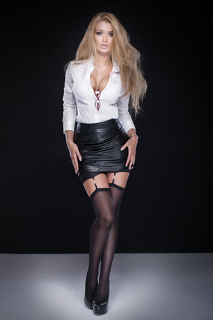 Sexy elegant businesswoman posing over black background, looking at camera.