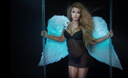 Reizvolle schöne blonde Frau in schwarzen Dessous posiert wie ein Engel. Standard-Bild - 38945685