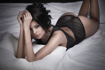 nude ass: Sexy beautiful brunette woman lying in bed in sensual black lingerie, looking at camera. Stock Photo