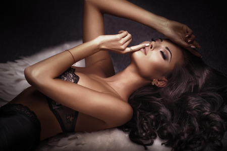 Beautiful sensual brunette woman posing in elegant lingerie. Lady with long healthy curly hair.