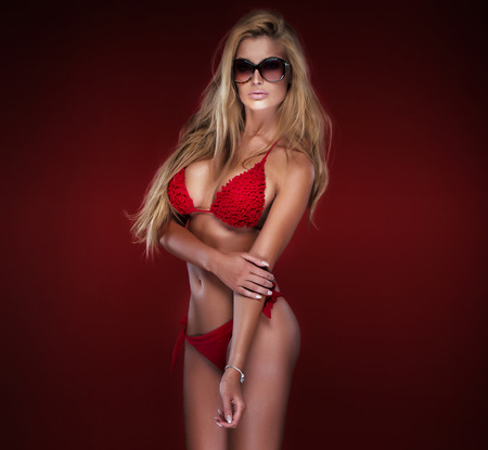 Sexy beautiful blonde woman posing in swimsuit over red background. Girl wearing fashionable sunglasses.Studio shot. photo