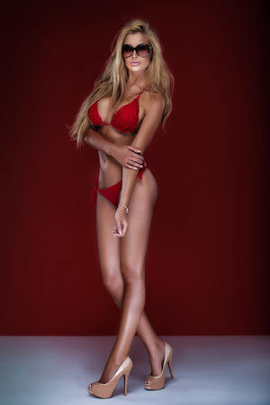 charming: Sexy beautiful blonde woman posing in swimsuit over red background. Girl wearing fashionable sunglasses.Studio shot.