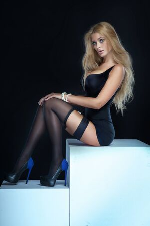 big breast woman: Sexy blonde woman sitting, wearing elegant lingerie and stockings. Studio shot. Stock Photo