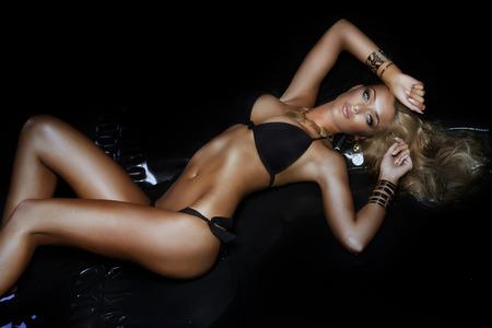 Beautiful woman posing in black simwear, looking at camera.
