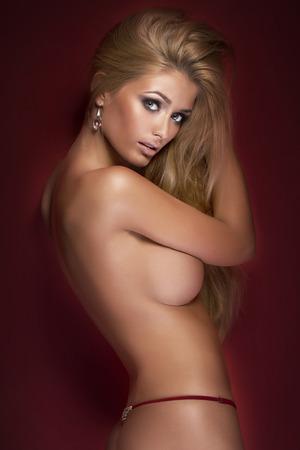 pechos: Sexy mujer rubia desnuda posando en el estudio. Señora con cuerpo delgado bronceada. Chica sonriendo, mirando a la cámara.