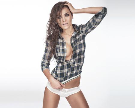 mojado: Mujer atractiva de moda que presenta con el pelo mojado en estudio, mirando a la c�mara.