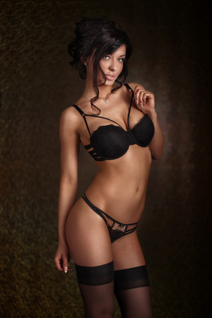 lenceria: Elegante mujer morena sensual posando en ropa interior negro sexy, mirando a la cámara. Estudio de disparo.