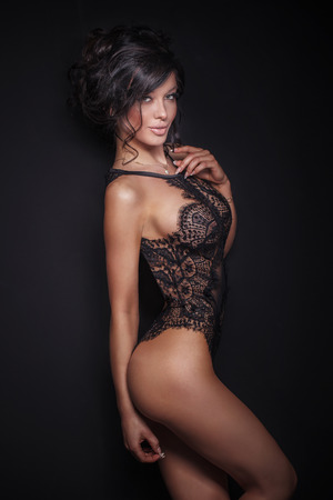 lingerie: Elegant sensual brunette woman posing in sexy black lingerie, looking at camera. Studio shot.